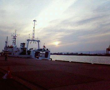 夕日と波と船